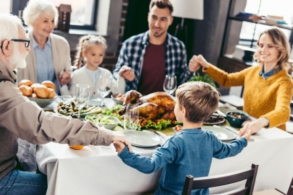 family holding hands together to pray while sitting in dinning table reflects christian parenting