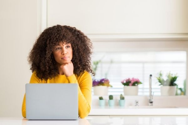 woman in front a laptop thinking for self-improvement