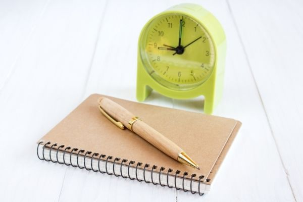 Clock behind notepad and pen for time management exercise