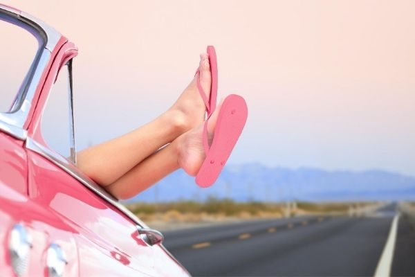 photo of woman's feet relaxing on top pink car door
